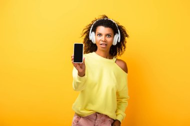 shocked african american woman in headphones holding smartphone with blank screen on yellow