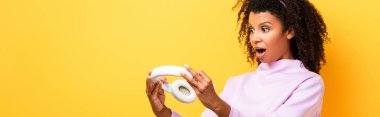 shocked african american woman holding wireless headphones on yellow, banner