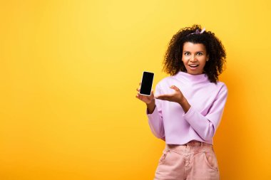 Excited african american woman pointing with hand at smartphone with blank screen on yellow stock vector