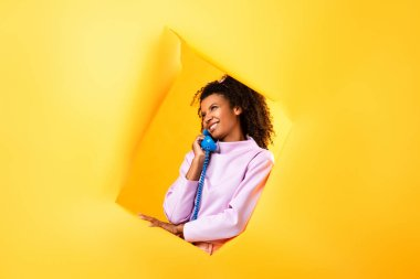Happy african american woman talking on retro telephone near hole in ripped paper on yellow background stock vector