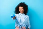 potěšen africký Američan žena drží retro telefon na modré