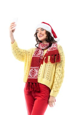 Pleased woman in santa hat and scarf taking selfie on smartphone isolated on white stock vector