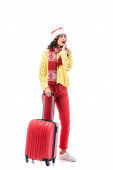 shocked young woman in santa hat and scarf with ornament standing with travel bag isolated on white