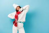 elégedett fiatal nő fehér téli ruhában, meleg sál, kesztyű és kalap kék