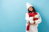 mladá potěšená žena v bílé zimní oblečení držení dárky na modré