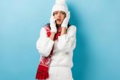 szomorú fiatal nő fehér téli ruha beszél okostelefon kék