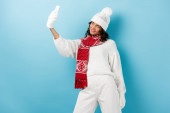 fiatal boldog nő fehér téli ruha csinál szelfi a kék