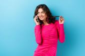 Photo joyful woman talking on smartphone and touching hair on blue