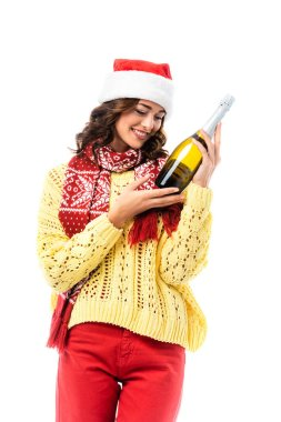 Joyful young woman in santa hat and scarf with ornament looking at bottle of champagne isolated on white stock vector