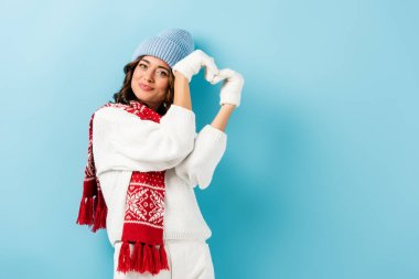Pleased young woman in winter outfit, warm scarf, gloves and hat showing heart sign on blue stock vector