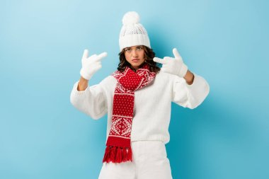 Displeased young woman in white winter outfit showing middle fingers on blue stock vector