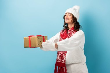 Young pleased woman in winter outfit with outstretched hands holding wrapped present on blue stock vector
