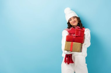 Young joyful woman in winter outfit holding presents on blue stock vector