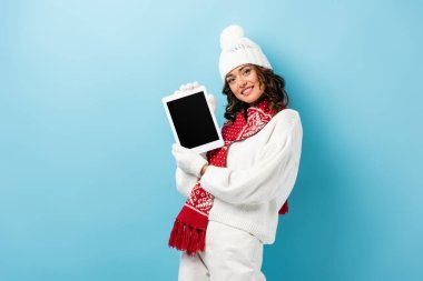 Joyful young woman in winter outfit holding digital tablet with blank screen on blue stock vector