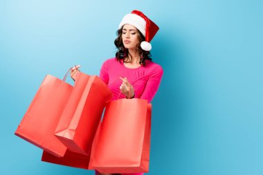 Young brunette woman in santa hat looking at shopping bags on blue stock vector