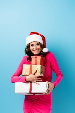 Joyful woman in santa hat and dress holding wrapped presents on blue stock vector