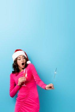 Şok olmuş Noel Baba şapkalı kadın elinde maytap ve mavi üzerine bir bardak şampanya tutuyor.
