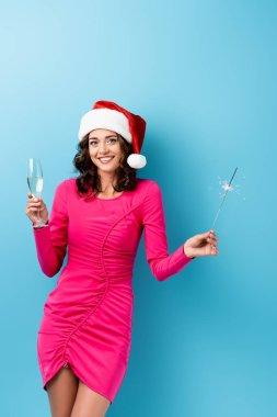 Noel Baba şapkalı neşeli kadın elinde maytap ve mavi üzerine bir bardak şampanya tutuyor.