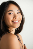 Photo brunette asian woman smiling while looking at camera isolated on white