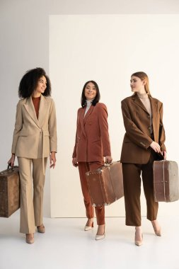 Full length of interracial women in trendy suits holding suitcases on white stock vector