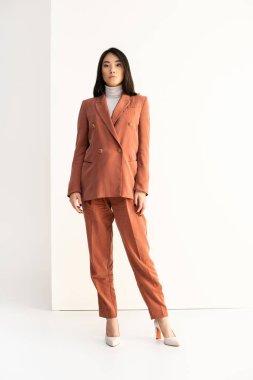 Full length of brunette asian woman in trendy suit posing on white stock vector