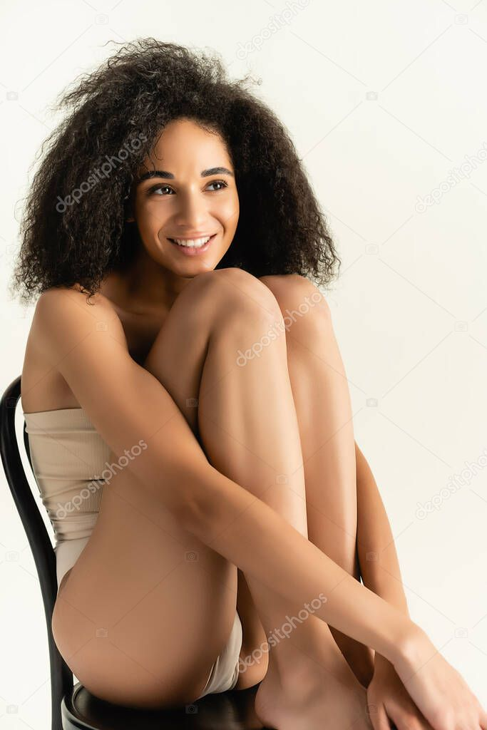 Curly african american woman in underwear smiling while posing on chair isolated on white stock vector
