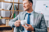 Young businessman smiling while holding cup of coffee in office