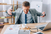 Angry businessman with smartphone looking at pouring out coffee on papers