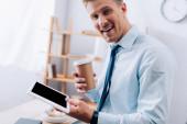 Veselý podnikatel s kávou jít a digitální tablet při pohledu na fotoaparát