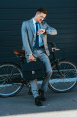 Businessman holding briefcase while looking at wristwatch near bicycle outdoors