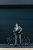 Young businessman holding briefcase while standing near bike and building
