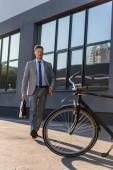 Podnikatel s kufříkem chůze na kole venku