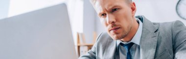 Focused businessman looking at laptop on blurred foreground in office, banner