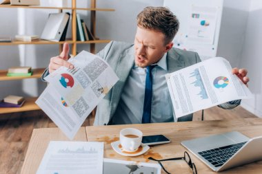 Aggressive businessman holding dirty documents near pouring out coffee and devices in office stock vector