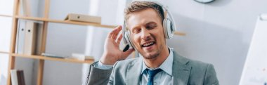 Positive businessman listening music in headphones in office, banner