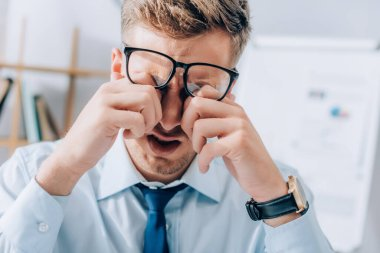Exhausted businessman rubbing eyes while working in office stock vector