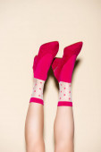 cropped view of female legs in pink retro socks and shoes on beige background