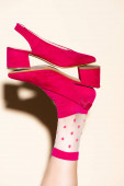 cropped view of female leg in pink retro socks and shoes on beige background
