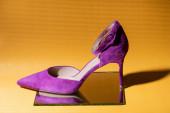 elegantní fialové semišové podpatky boty na zrcadle na žlutém pozadí