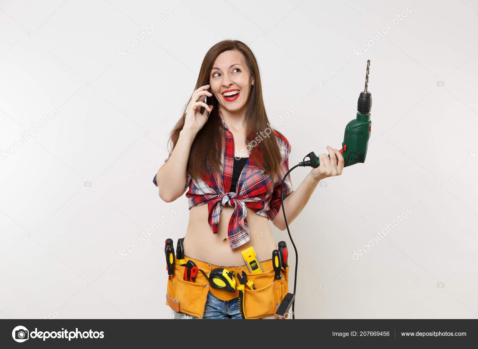 2564ea627a76 Une énergie jeune bricoleur femme en chemise à carreaux, ceinture d outils  kit complet d instruments parler sur téléphone mobile, posséder perceuse ...