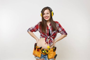 Handyman woman in shirt, denim shorts, noise insulated headphones, kit tools belt full of instruments standing with arms akimbo isolated on white background. Female in male work. Renovation concept