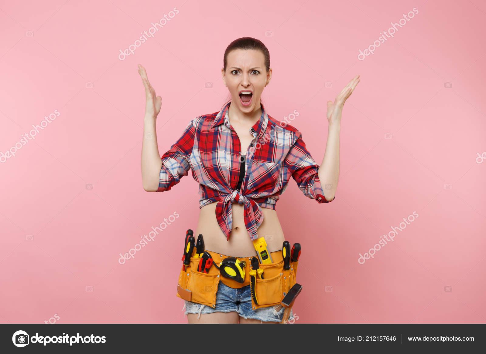58d76b018422 Femme forte jeune bricoleur portant la chemise à carreaux, short en Jean, ceinture  d outils kit complet d instruments utiles divers isolés sur fond rose.
