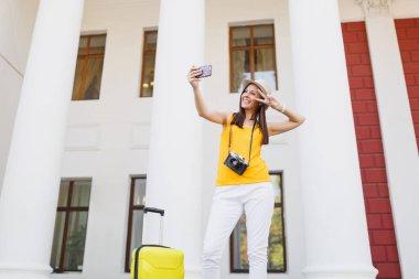Traveler tourist woman doing take selfie shot talking on mobile phone, calling friend, booking taxi, hotel on mobile phone outdoor. Girl traveling abroad on weekend getaway. Tourism journey lifestyle
