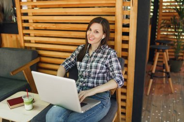 Woman in outdoors street summer coffee shop wooden cafe sitting in casual clothes, working on modern laptop pc computer, relaxing during free time. Mobile Office. Lifestyle freelance business concept