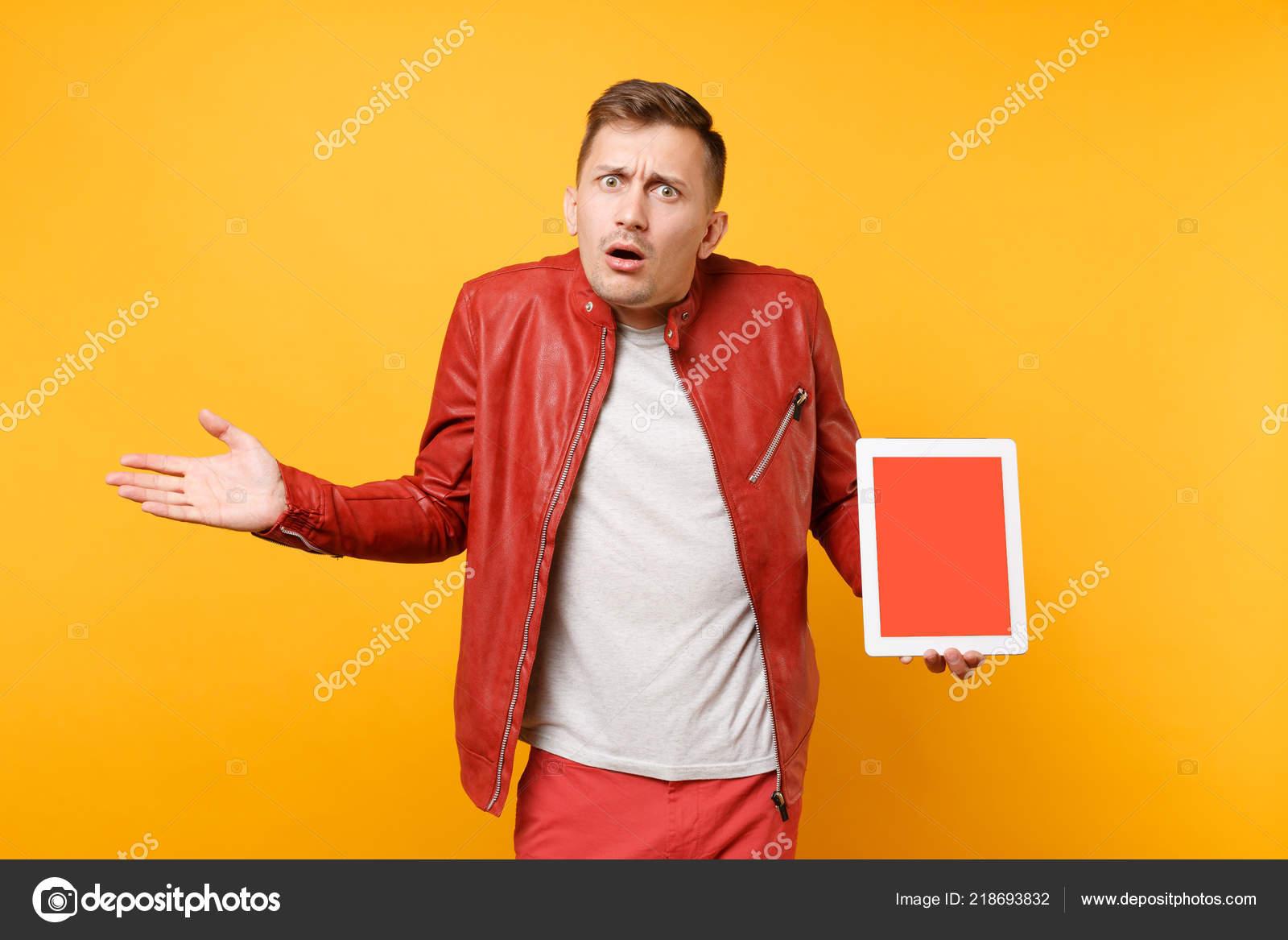 a3872205e4c61 Diversión de moda retrato joven en cuero rojo chaqueta camiseta hold tablet  pc teclado con pantalla en blanco vacía aislada sobre fondo amarillo  brillante.
