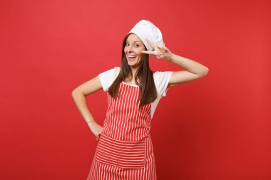 Housewife female chef cook or baker in striped apron white t-shirt toque chefs hat isolated on red wall background. Beautiful housekeeper woman showing victory sign at eye. Mock up copy space concept