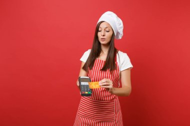 Housewife female chef cook or baker in striped apron t-shirt toque chefs hat isolated on red wall background. Woman hold hand bank payment terminal credit card nfc device. Mock up copy space concept