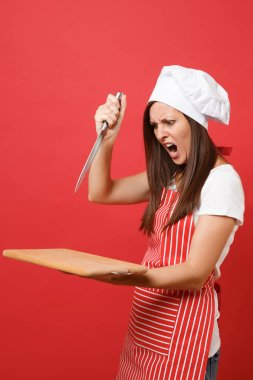 Housewife female chef cook or baker in striped apron white t-shirt, toque chefs hat isolated on red wall background. Angry screaming woman hold wooden cutting board, knife. Mock up copy space concept
