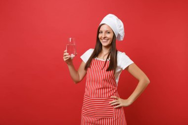 Housewife female chef cook or baker in striped apron white t-shirt toque chefs hat isolated on red wall background. Woman holding drinking clear fresh pure water from glass Mock up copy space concept