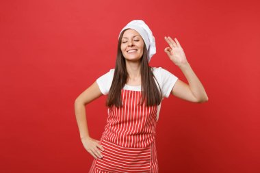 Housewife female chef cook or baker in striped apron white t-shirt, toque chefs hat isolated on red wall background. Smiling calm cute woman making okay taste delight sign. Mock up copy space concept
